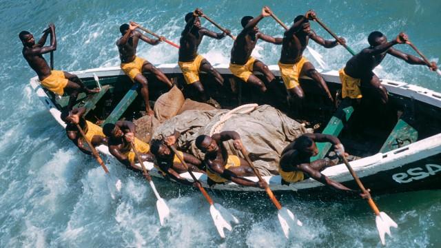 Fanti fishermen rowing a skiff, Ghana, Africa .